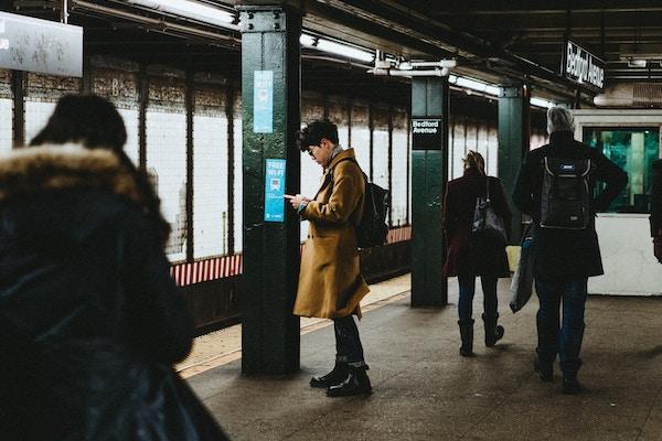 man using phone on the subway